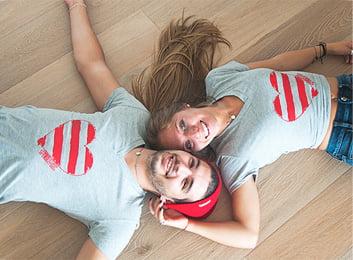 Un hombre y una mujer sonrientes, luciendo camisetas grises con un corazon de lineas rojas.