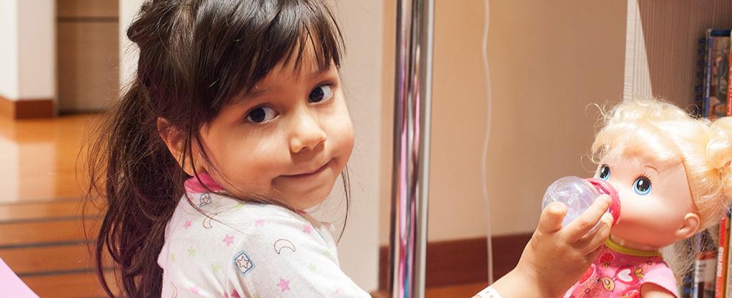 Nina tímidamente mira a la cámara mientras le da tetero a su muñeca.