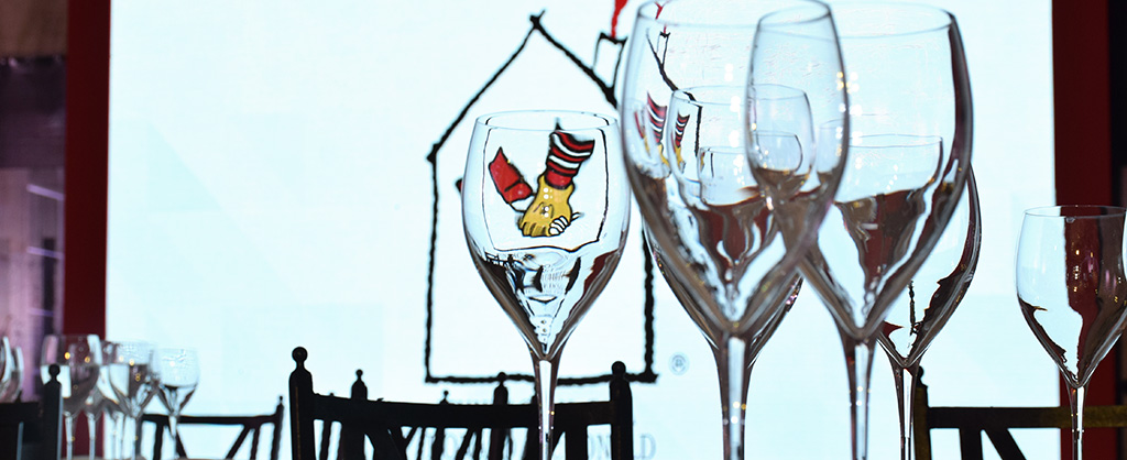 Copas de vino aparecen delante de la fotografía. Detrás y a través de una de ellas se refleja en logo de la organización Ronald McDonald House Charities.