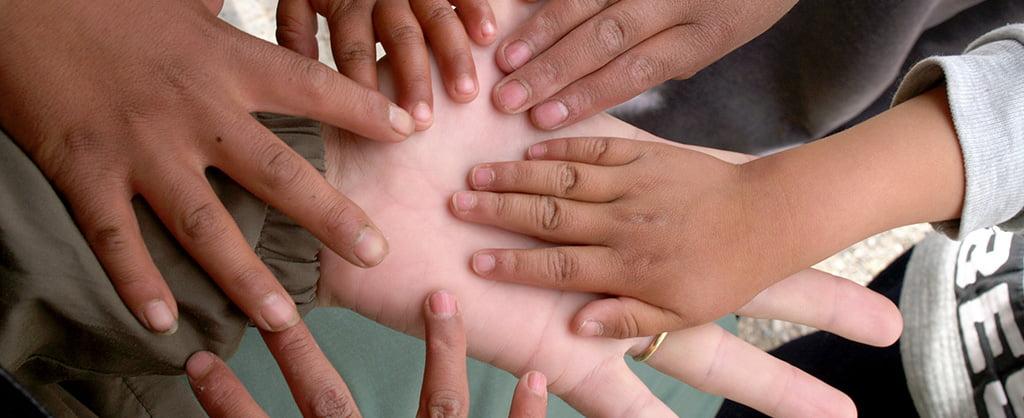 La mano de un adulto extendida hacia arriba y sosteniendo las manos de varios niños.