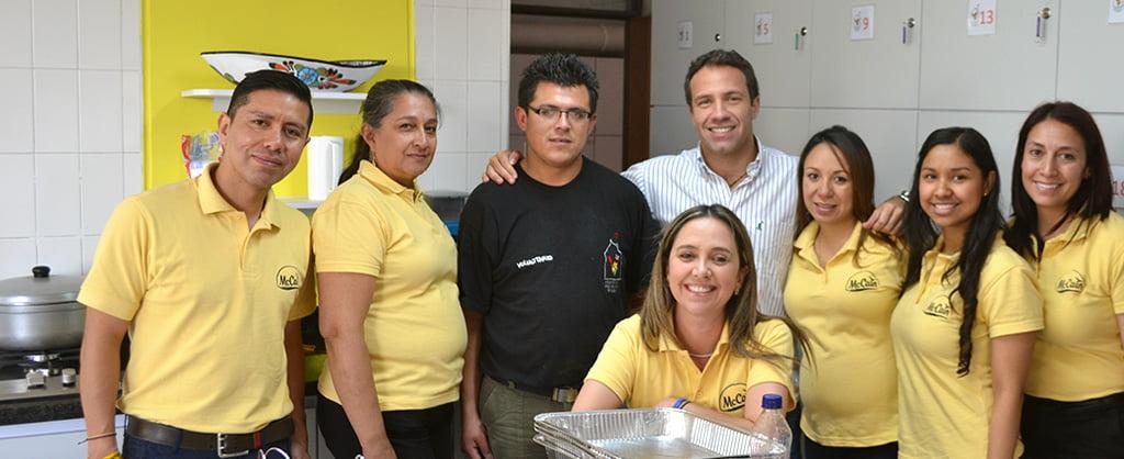 Mujeres y hombres en camisetas amarillas, sirviendo como voluntarios del programa de comidas que benefician a las familias de la Casa Ronald McDonald.