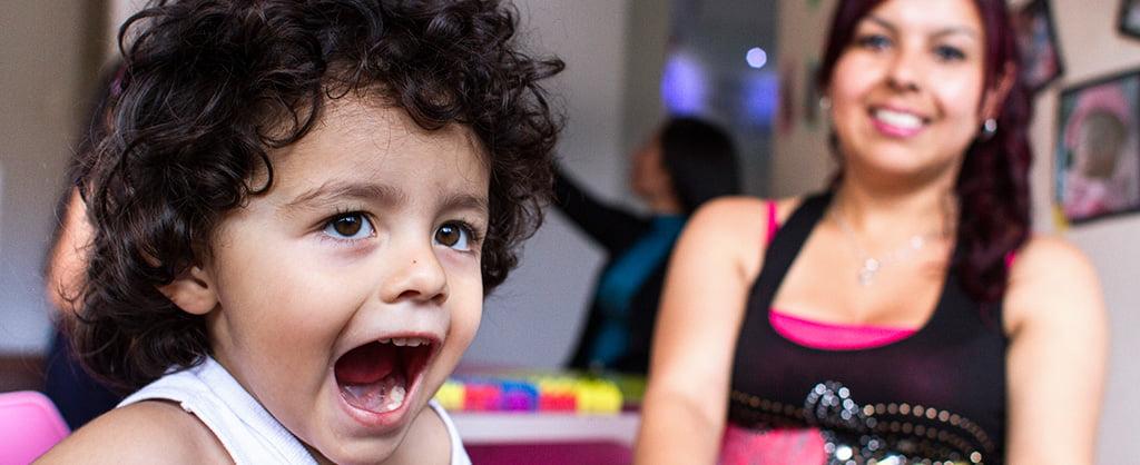 Una madre mira a su hijo mientras grita entusiasmado.