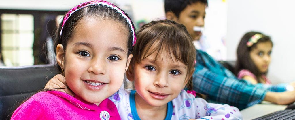 Varios niños en la parte de atrás de la fotografía. Adelante, aparecen dos niñas, una de ellas abrazando a la otra; ambas están sonriendo.