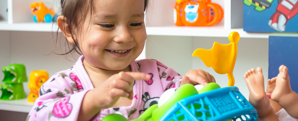 Pequeña niña sonriendo, jugando con varios juguetes coloridos.