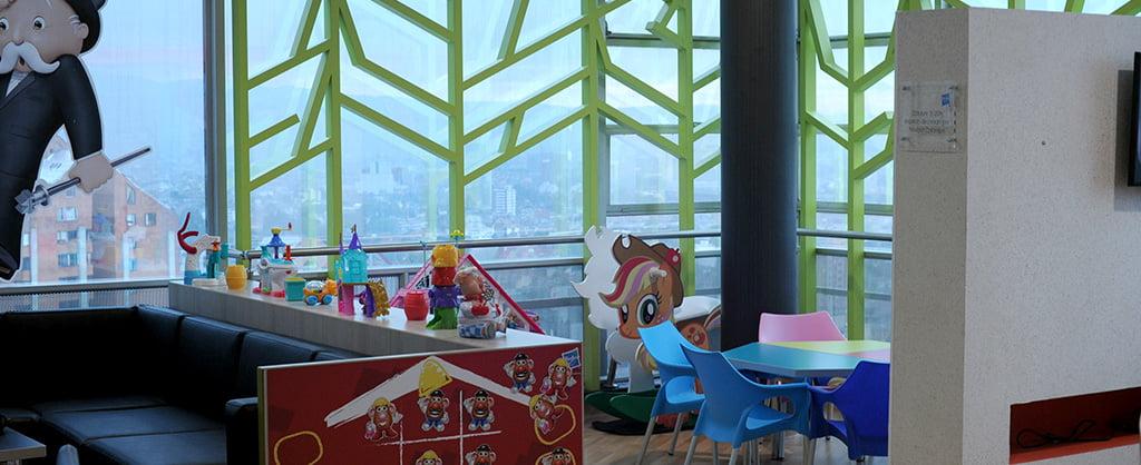 Interior de una Sala Familiar Ronald McDonald donde hay un sillón, juegues y una mesita con sillas para los niños. Hay una ventana grande donde se divisa el centro de la ciudad.