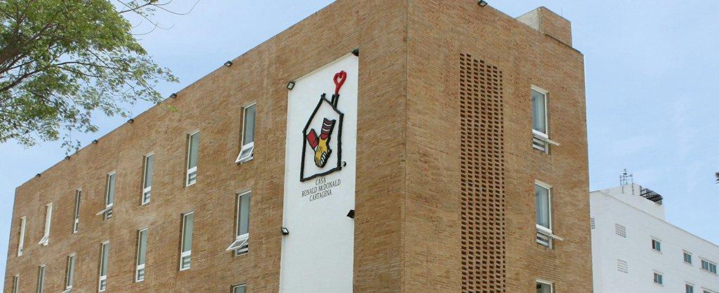 El programa Casa Ronald McDonald en Cartagena; el logo del programa aparece en la parte de adelante del edificio de ladrillo.