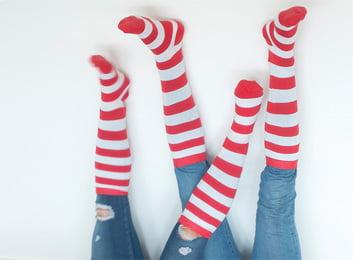 Las piernas de dos personas luciendo los medios de Ronald McDonald con rayas rojas y blancas.